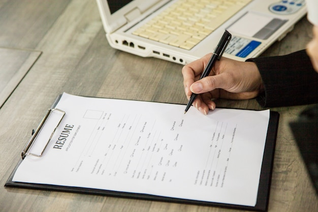 Kierownik kobieta pisze i sprawdza cv od personelu, pracownicy z kawą sprawdzają aplikację.