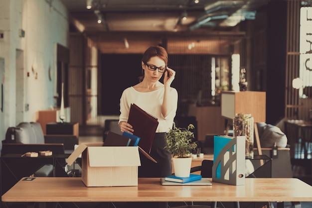 Kierownik kobieta układa rzeczy w miejscu pracy.