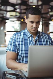 Kierownik korzystający z laptopa w kafeterii