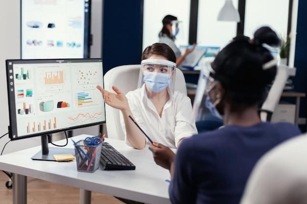 Kierownik noszący maskę na twarz dla covid19 wyjaśniający afrykańskiemu pracownikowi wykres finansowy. wieloetniczny zespół pracujący w firmie z nową normą szanującą dystans społeczny z powodu globalnej pandemii z cor