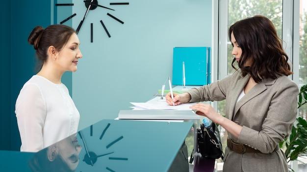 Kierownik pokazuje książeczkę rejestracyjną klientowi w recepcji