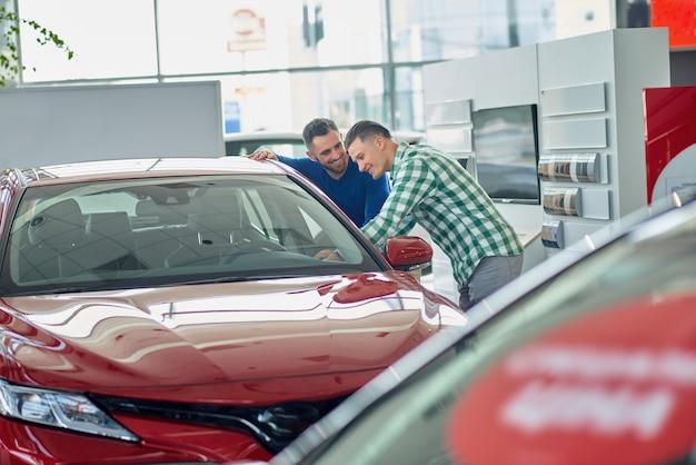 Kierownik pomaga klientowi wybrać pojazd i pokazuje projekt.
