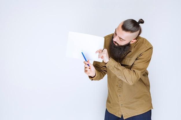 Kierownik projektu pokazujący raporty swojemu koledze i zaznaczający błędy lub poprawki.