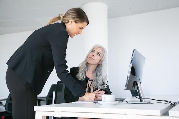 Kierownik projektu składający podpis na raporcie pracowników. żeńskie koledzy z pracy siedząc i stojąc w miejscu pracy z monitorem i filiżanką kawy. koncepcja komunikacji biznesowej