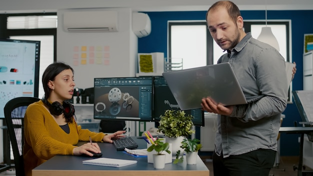 Kierownik projektu trzymający laptopa i rozmawiający z inżynierem porównującym przemysłowe elementy...
