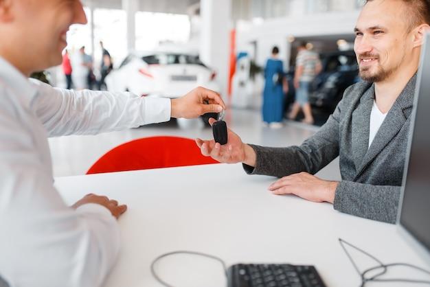 Kierownik przekazuje kupującemu klucz, nowy samochód w salonie.