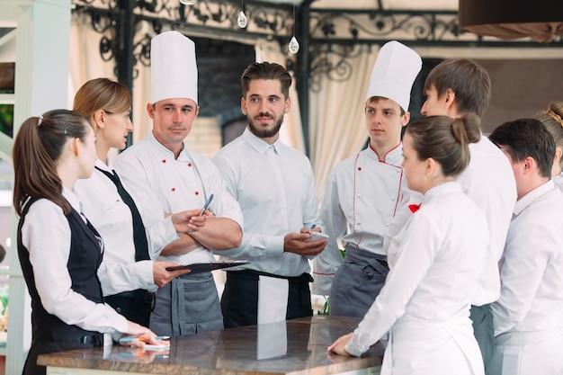 Kierownik restauracji i jego personel na tarasie. interakcja z szefem kuchni w restauracji.