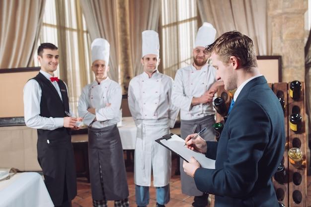 Kierownik restauracji i jego personel w kuchni.