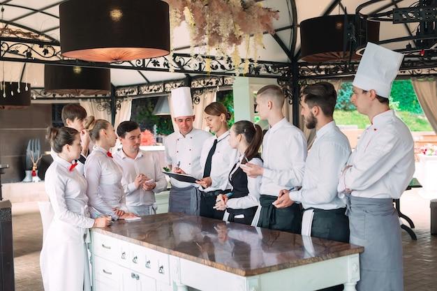 Kierownik restauracji i jego pracownicy na tarasie, wchodząc w interakcje z szefem kuchni w restauracji,