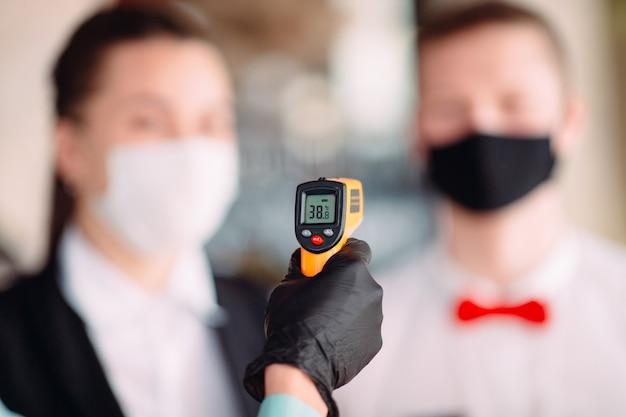 Kierownik restauracji lub hotelu sprawdza temperaturę ciała personelu za pomocą termowizora.