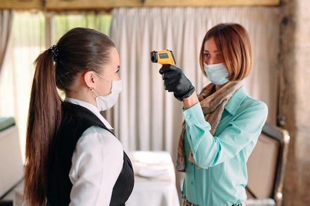 Kierownik restauracji lub hotelu sprawdza temperaturę ciała personelu za pomocą urządzenia do obrazowania termicznego.