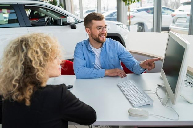 Kierownik salonu samochodowego z klientem przy komputerze w salonie