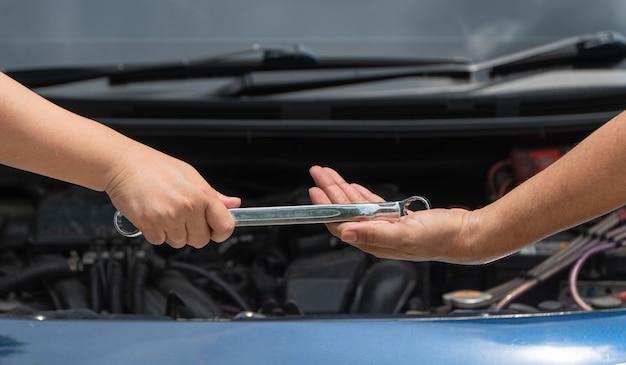Kierownik serwisu naprawczego silnika samochodowego wysyła klucz do współpracownika.