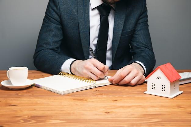Kierownik sprzedaży lub pośrednik w obrocie nieruchomościami, szczegółowo opisujący warunki zakupu domu z promocjami ubezpieczeniowymi