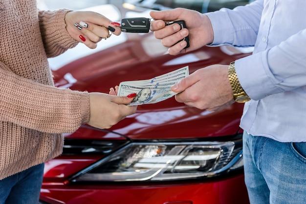 Kierownik sprzedaży przekazujący kluczyki z samochodu do klienta