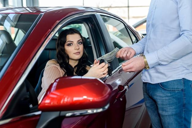 Kierownik sprzedaży rozdający kluczyki od samochodu klientowi