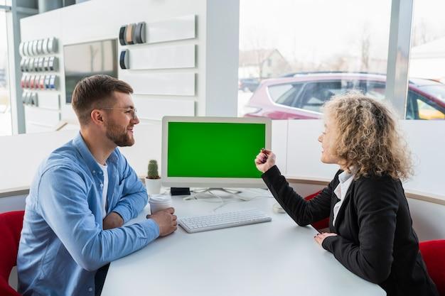 Kierownik sprzedaży samochodów z klientem przy komputerze w salonie