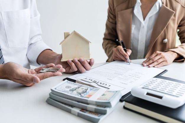 Kierownik sprzedaży trzymający klucze do akt dla klienta po podpisaniu umowy najmu najmu lub sprzedaży