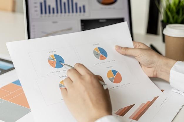 Kierownik sprzedaży wskazuje na podsumowanie sprzedaży, sprawdza sprzedaż każdego oddziału, sprawdza informacje przed przedstawieniem ich na spotkaniu kierownictwu. koncepcja zarządzania sprzedażą.