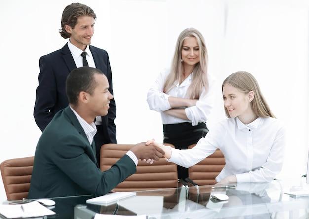 Kierownik uścisk dłoni i klient w biurze