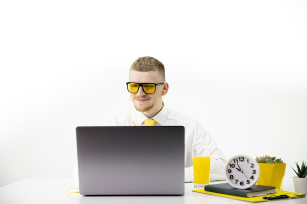 Kierownik uśmiecha się patrząc na laptopa w biurze, akcent na żółty soku krawat puli