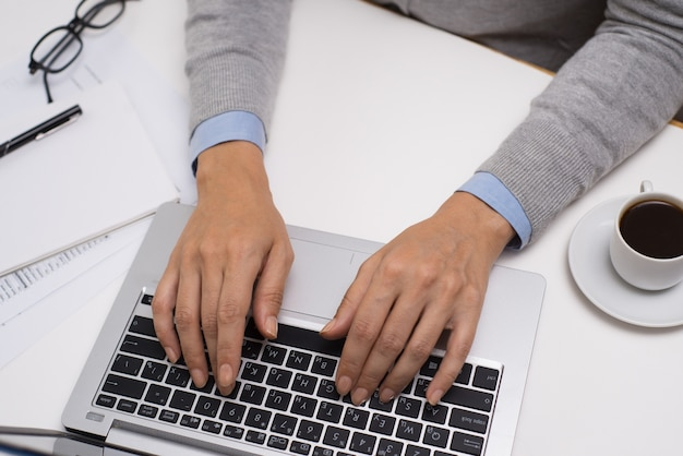 Kierownik używa laptop przy stołem