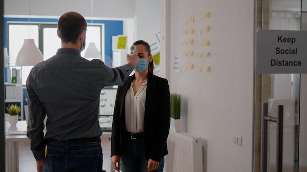 Kierownik w masce ochronnej sprawdza temperaturę kolegów termometrem na podczerwień przed wejściem do biura podczas pandemii koronawirusa. współpracownicy utrzymujący dystans społeczny w celu zapobiegania covid19