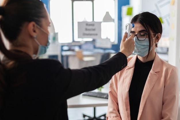 Kierownik wykonawczy mierzący temperaturę za pomocą termometru medycznego na podczerwień, aby zapobiec zakażeniu koronawirusem przed wejściem do biura firmy startowej. kobieta z maską ochronną