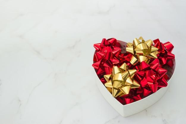 Kierowy prezenta pudełko z świątecznymi łękami inside na bielu wykładamy marmurem tło, selekcyjna ostrość, kopii przestrzeń. miłość i motyw walentynek.