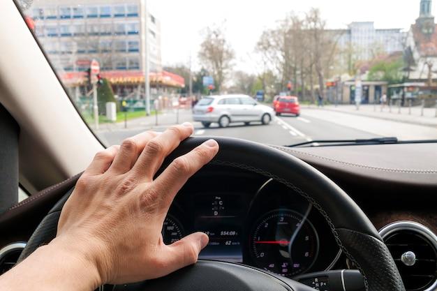 Kieruj kołem z ręką kierowcy w nowoczesnym wnętrzu samochodu z widokiem na ulicę