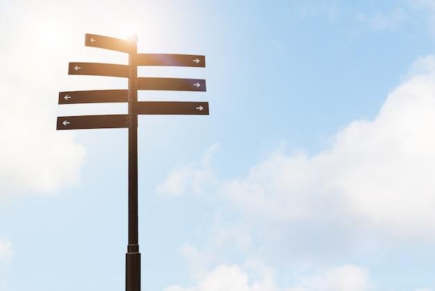 Kierunkowskaz przewdonika kierunku znak na słupie z niebieskiego nieba tło