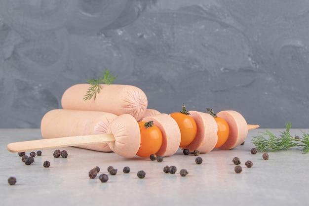 Kij pokrojony w plasterki kiełbaski z pomidorami na marmurowym tle.