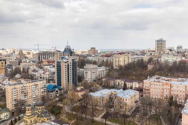 Kijów, ukraina - 01 kwietnia 2020: widok z lotu ptaka na dachy i ulice miasta kijów. stara i nowoczesna architektura centrum kijowa. widok z parus business center