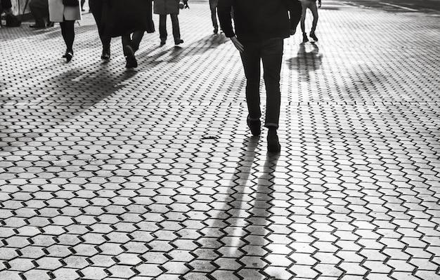 Kijów, ukraina - 10 listopada 2018: światło i cienie w kijowie. sylwetki ludzi spacerujących po ulicach wielkiego miasta i oświetlone tylnym światłem. cienie ludzi spacerujących po ulicy w wieczornym świetle.