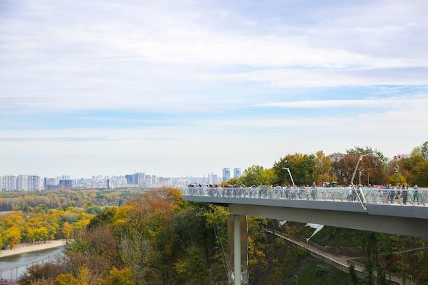Kijów, ukraina - 12 października 2019: most kijowski w pobliżu łuku przyjaźni narodów. jesienna stolica ukrainy. turyści robiący zdjęcia.