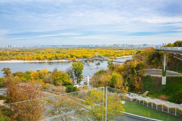 Kijów, ukraina - 12 października 2019: widok z mostu w kijowie w pobliżu łuku przyjaźni narodów. jesienna stolica ukrainy. krajobraz miasta z rzeką dniepr.