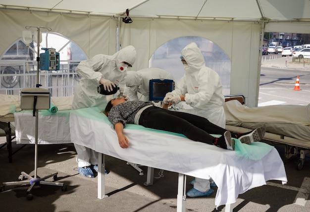 Kijów, ukraina - 12 października 2021: aktywiści występują ze sceną tymczasowego oddziału resuscytacji dla pacjentów z covid-19. lekarze przeprowadzają u pacjenta resuscytację w trybie nagłym