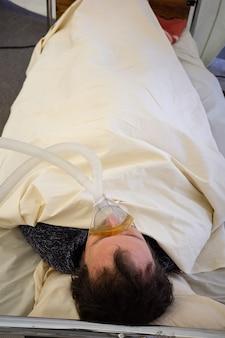 Kijów, ukraina - 12 października 2021: aktywiści występują ze sceną tymczasowego oddziału resuscytacji dla pacjentów z covid-19. mężczyzna z maską tlenową