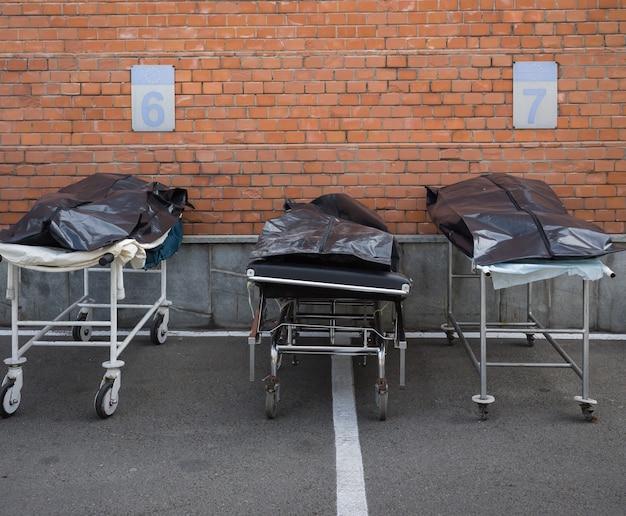 Kijów, ukraina - 12 października 2021: aktywiści występują ze sceną tymczasowego oddziału resuscytacji dla pacjentów z covid-19. śmierć wzrasta z każdym dniem. personel owinął martwe ciała