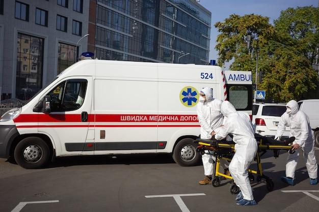 Kijów, ukraina – 12 października 2021 r.: zespół pogotowia przenosi pacjenta na noszach z samochodu do mobilnego szpitala podczas epidemii covid-19