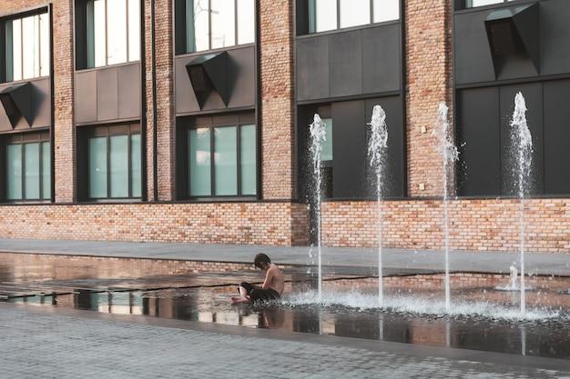 Kijów, ukraina - 28 lipca 2020 r.: dzieci bawiące się w fontannie i cieszące się chłodnymi strumieniami wody w upalny dzień. gorące lato. fontanny w pobliżu fabryki roshen w kijowie