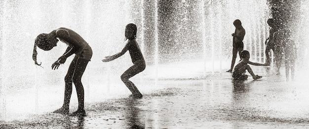 Kijów, ukraina - 29 lipca 2020 r.: dzieci bawiące się w fontannie i cieszące się chłodnymi strumieniami wody w upalny dzień. gorące lato. fontanny w pobliżu fabryki roshen w kijowie