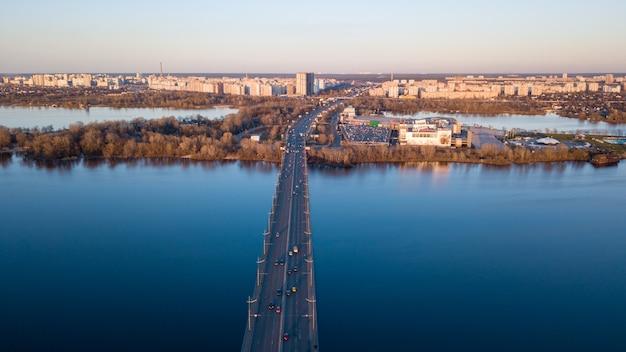Kijów, ukraina, 4 kwietnia: północny most na rzece dniepr z ruchem samochodowym z widokiem na lewą część kijowa i centrum handlowe skaimol na ukrainie