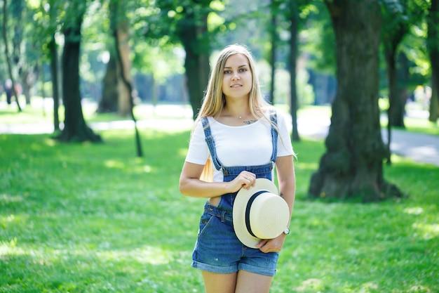 Kijów, ukraina - sierpień 2019 młoda piękna dziewczyna w dżinsowych kombinezonach i lekkiej czapce spacerująca po parku