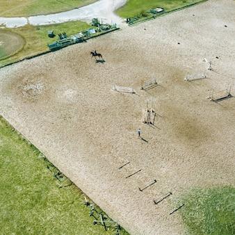 Kijów, ukraina, tor wyścigowy w słoneczny dzień, koń na torze podczas treningu. odbicie cieni na ziemi. fotografia dronem