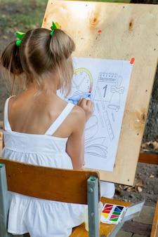 Kijów - wrzesień 2019: dziewczyna rysuje kolorowankę do 1 września