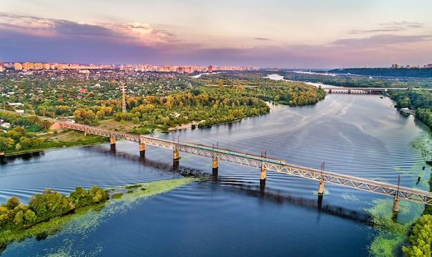 Kijowski miejski pociąg elektryczny na moście kolejowym pietrowski przez dniepr na ukrainie