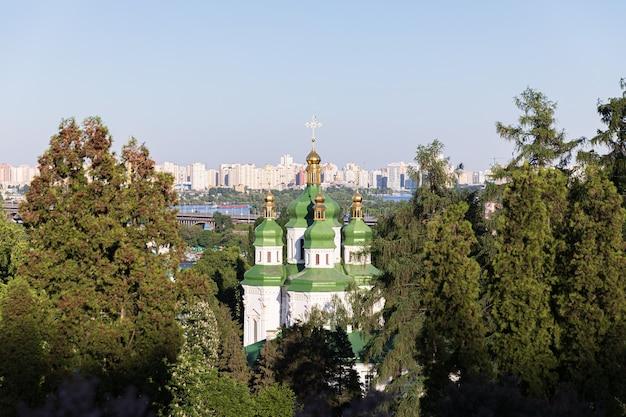 Kijowskie krajobrazy. wiosenny widok klasztoru vydubychi i rzeki dnipro z różowym i białym bzem kwitnącym w ogrodzie botanicznym w mieście kijów, ukraina