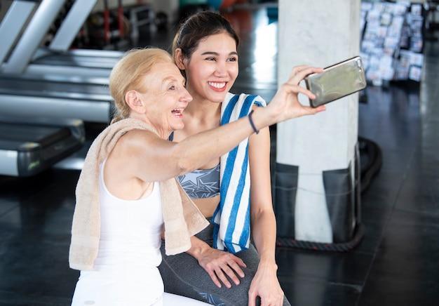 Kilka atrakcyjnych kobiet uśmiechniętych, biorąc selfie na smartfonie w siłowni fitness.