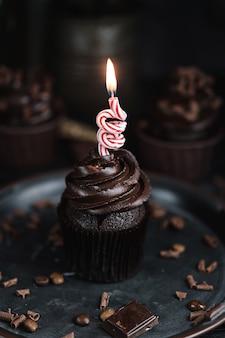 Kilka babeczek lub babeczek z kremem w kształcie czekolady na czarnym stole. świąteczna świeca pali się na torcie czekoladowym
